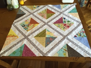 Finished quilt top with grey diagonal sashing