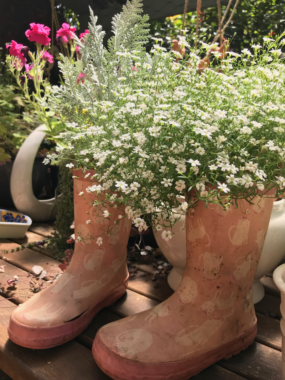 White flowers planted in old gumboots